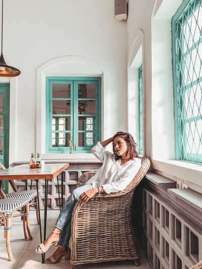 Portrait of woman sitting on window