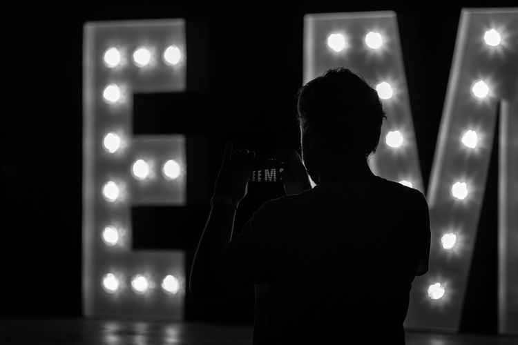Rear View Of Silhouette Man Photographing Illuminated Text At Night