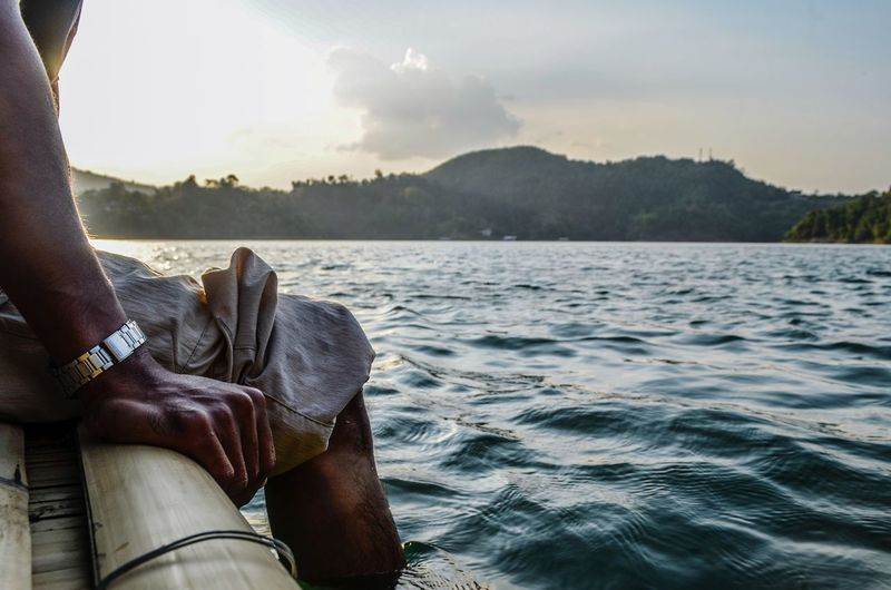Midsection of man sitting on wooden raft in lake