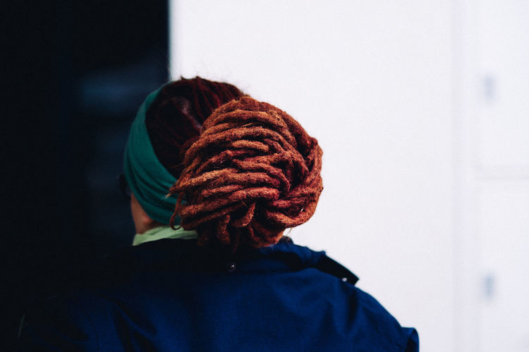 Rear view of woman with dreadlocks against wall