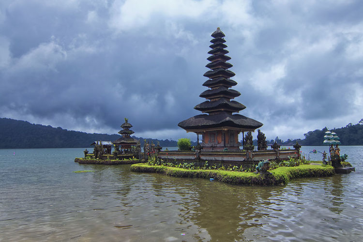 Traditional building by lake against cloudy sky