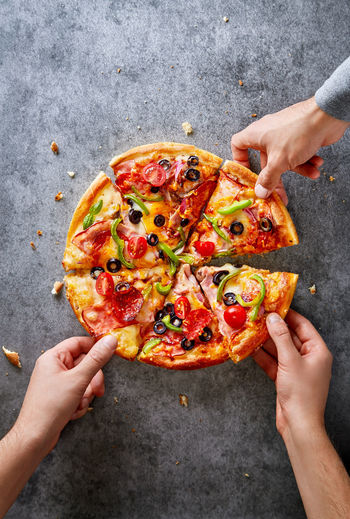 Pizza on a dark gray background viewed from above. Copy space. Top view Pizza Food Italian Food Freshness Human Hand Human Body Part Hand Holding People SLICE High Angle View Unhealthy Eating Ready-to-eat Men Human Limb Directly Above Eating Pizza Party! Pizza Time Copy Space