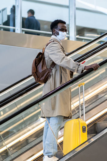 Man wearing mask standing on escalator
