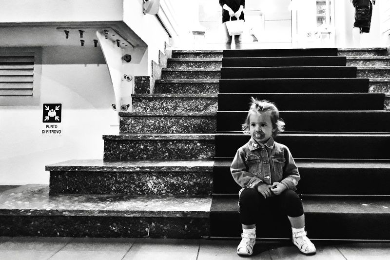 Cute girl with pacifier sitting on stairs