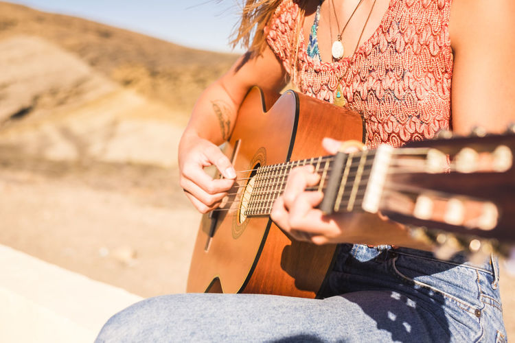 Midsection of woman playing guitar against mountain