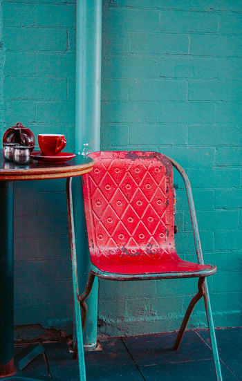 Empty Chair Against Turquoise Wall