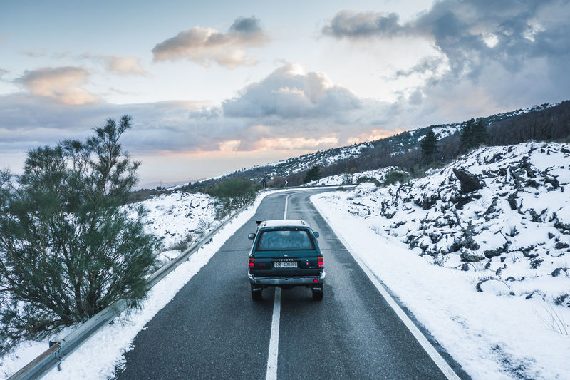 Car on road by snowcapped mountain against sky
