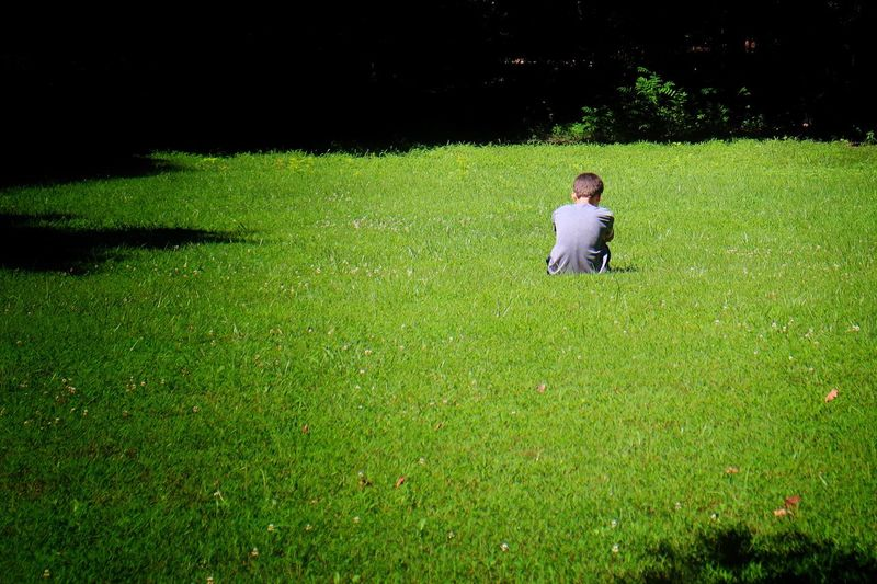 Pondering Thinking Alone Field Boy Green Color Plant Grass One Person Real People Field Leisure Activity Lifestyles Outdoors Casual Clothing