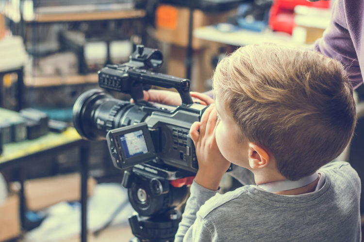 Rear view of boy using video camera