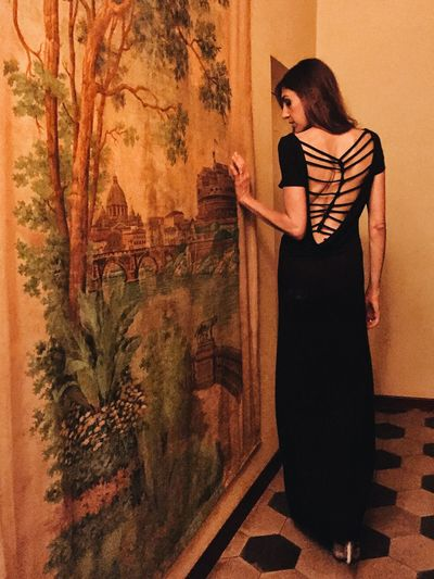 Full length rear view of beautiful woman walking by painting on wall