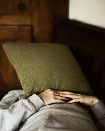 Man face covered with pillow sleeping at home
