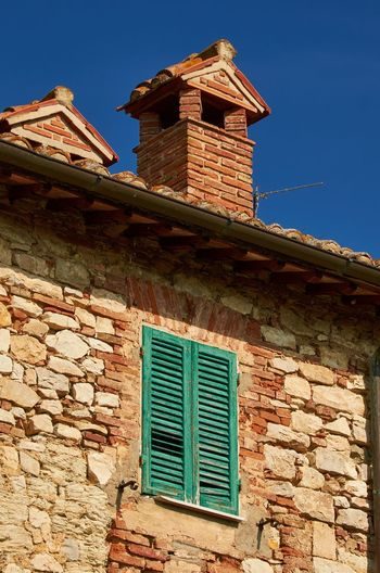 Castiglione del Lago, Umbria Italy Castiglione Del Lago Umbria House Façade Building Building Exterior Bricks Window Shutter Roof Historic Blue Sky Colorful Vivid Architecture No People Textures And Surfaces Gutter Tiles Chimney Smoke Stack