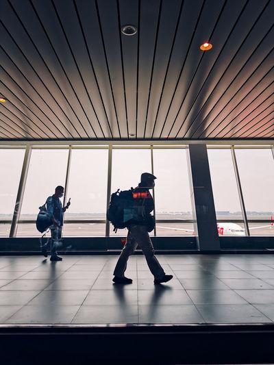 Rear view of men walking in airport