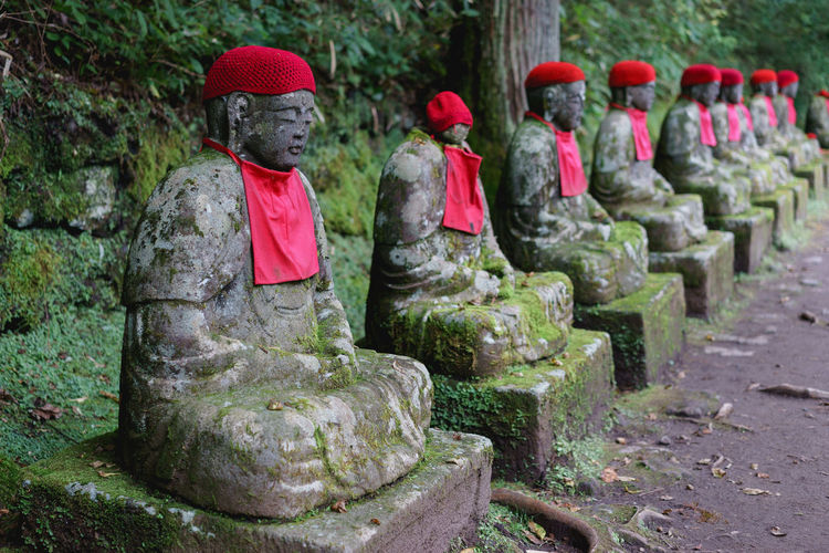 Old mossy statues in row at forest