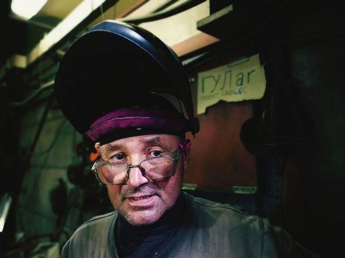 Portrait of man wearing hat in factory