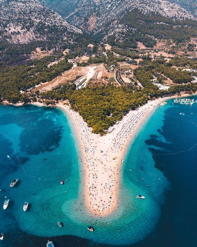 View over bol, croatia with drone capturing turquoise adriatic sea and beach life during the summer.