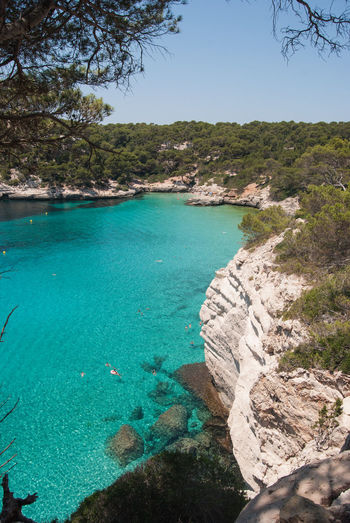Cala Mitjana Bay Beach Beauty In Nature Blue Day High Angle View Land Menorca Beach Nature No People Outdoors Plant Rock Rock - Object Scenics - Nature Sea Sky Solid Swimming Pool Tranquil Scene Tranquility Tree Turquoise Colored Water