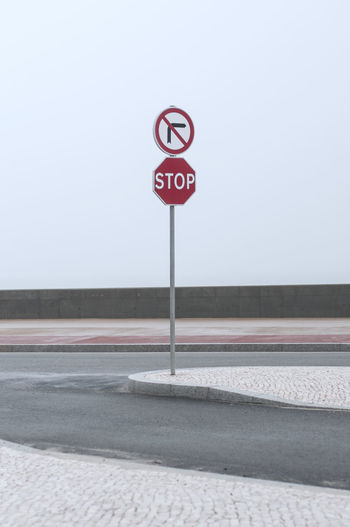 road sign at the atlantic Asphalt Atlantic Ocean Cloudy Gray Sky Portugal Sidewalk Sign Traffic Transportation Travel Car Cobblestone Day Furadouro No People Outdoors Red Road Road Sign Sea Sky Stop Sign Street Symbol Warning Sign