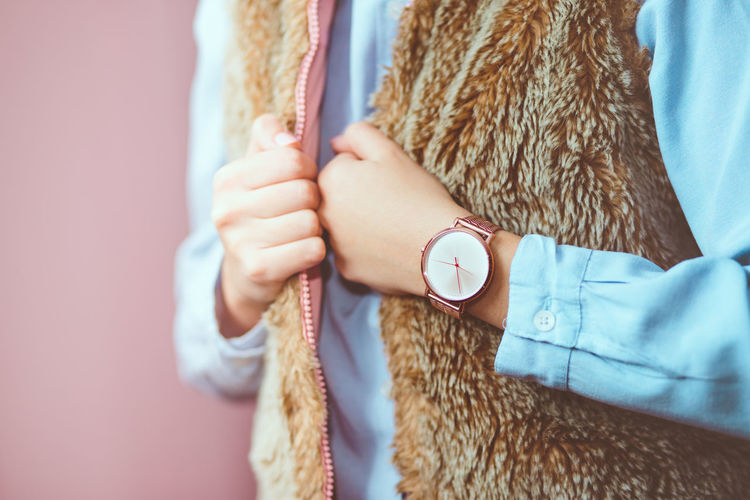Midsection Of Woman Wearing Fur Coat And Wristwatch