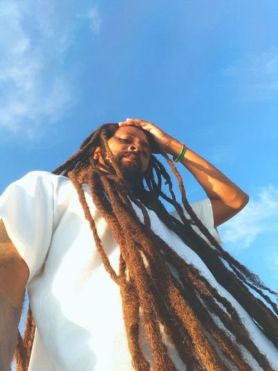 Low Angle View Portrait Of Mature Man With Dreadlocks Against Blue Sky