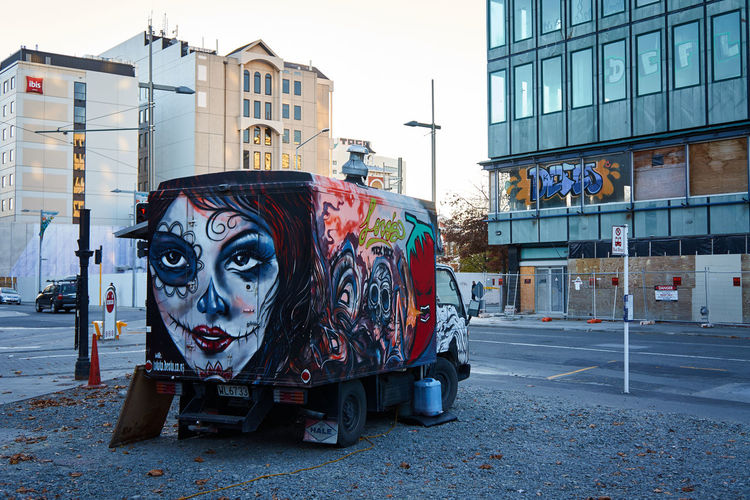 Graffiti on food truck parked at roadside in city