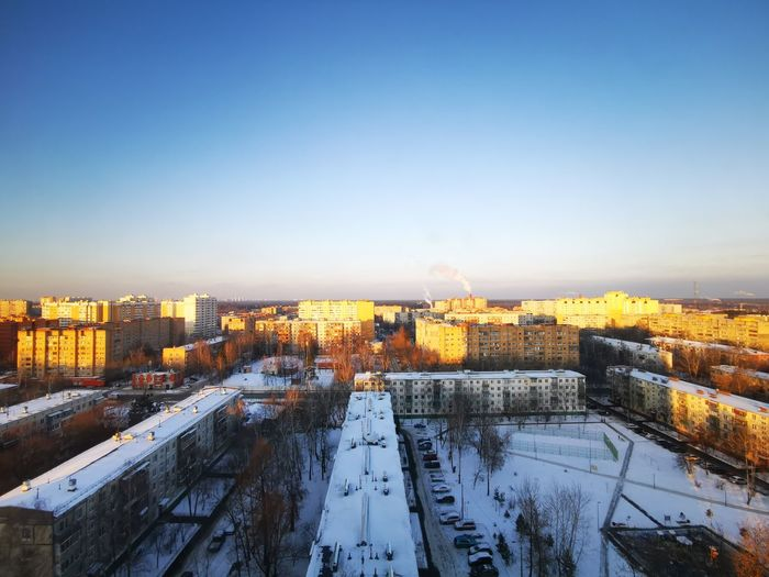 High angle view of snow covered buildings against sky during sunset