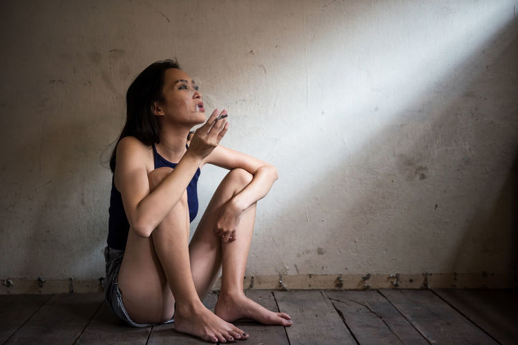 Stress Asian beautiful woman sitting and smoking cigarette near dirty wall with sunlight through window. girl exhaling smoke. Health care for World No Tobacco Day on 31 May every year. Adult Beautiful Woman Cigarette  Contemplation Depression - Sadness Emotion Flooring Full Length Hairstyle Home Interior Indoors  Leisure Activity Lifestyles Looking Away One Person Real People Sadness Sitting Tabacco  Wall - Building Feature Window Women Young Adult Young Women