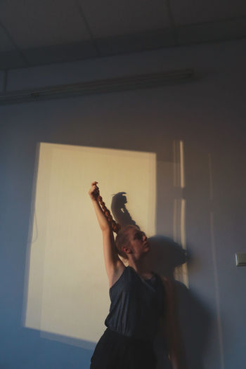 Woman with braided hair and hand raised standing against wall
