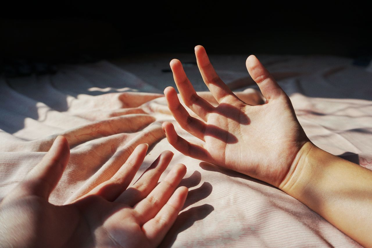 Cropped hands of people on bed at home