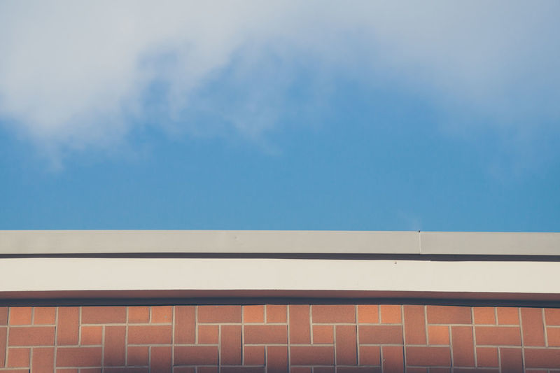 High section of wall against blue sky