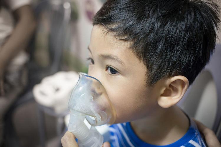 Close-up of boy wearing asthma inhaler