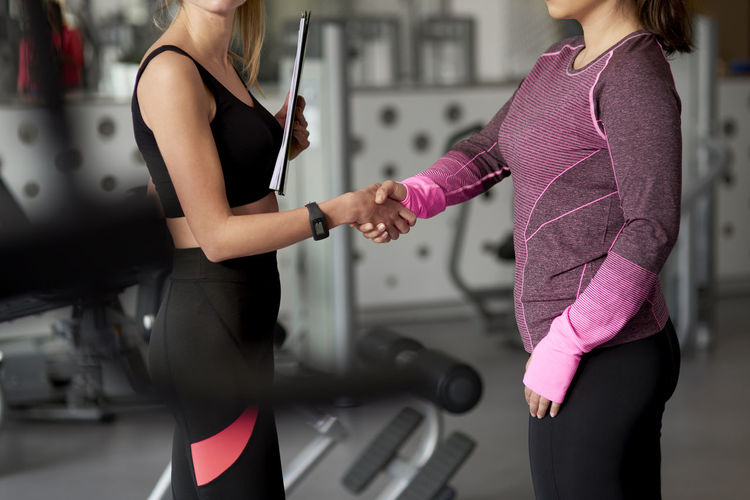 Midsection of women handshaking in gym