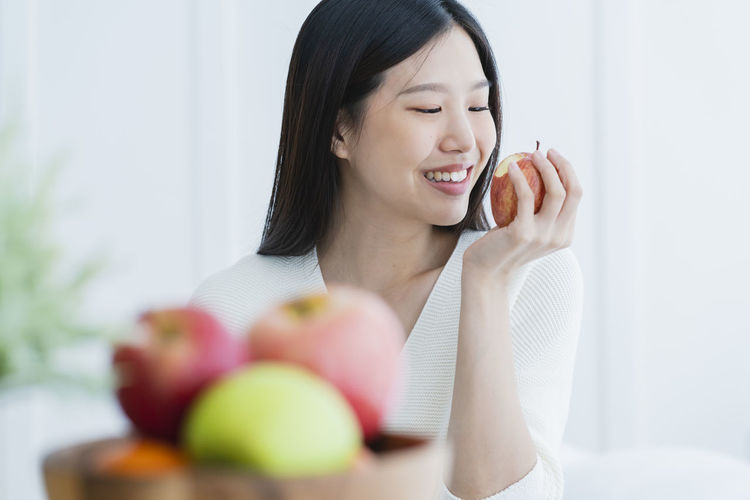 Smiling young woman holding apple at home