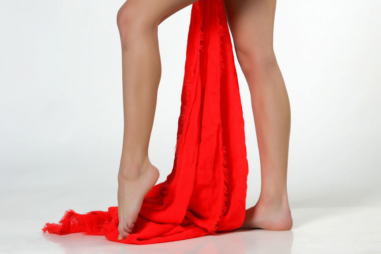 Low section of woman wearing high heels standing against white background