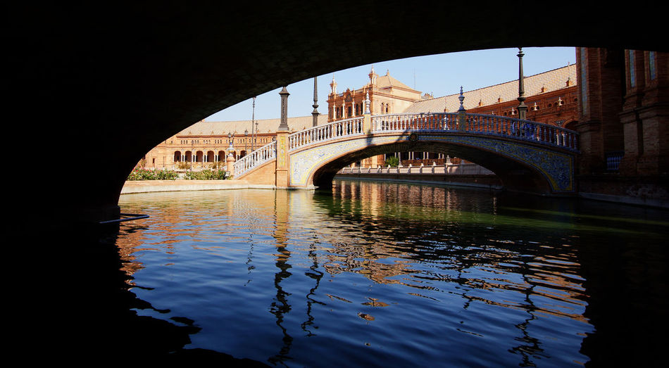 Below view of bridge over river at plaza de espana against clear sky