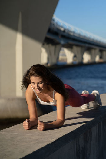 Full length of woman exercising against bridge and sky