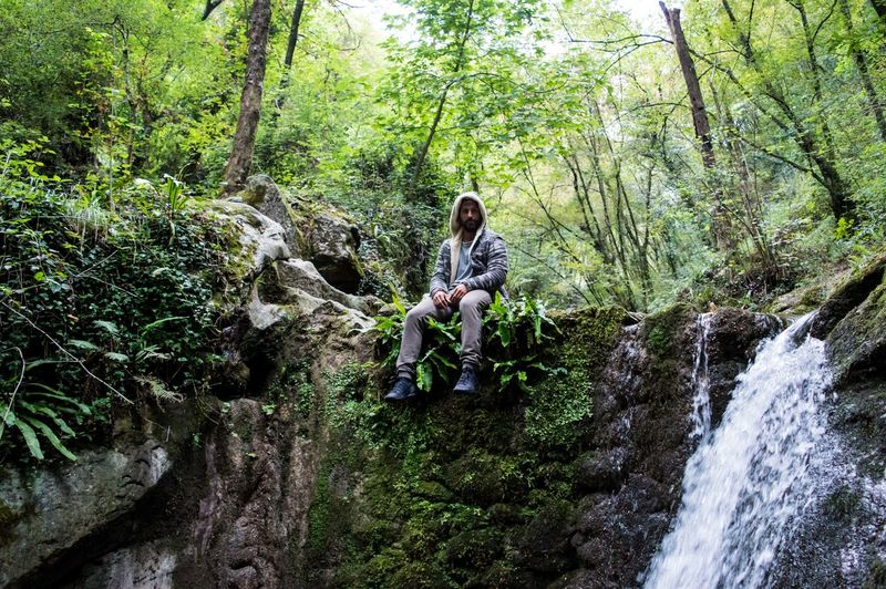 Full Length Of Man Sitting By Waterfall At Forest