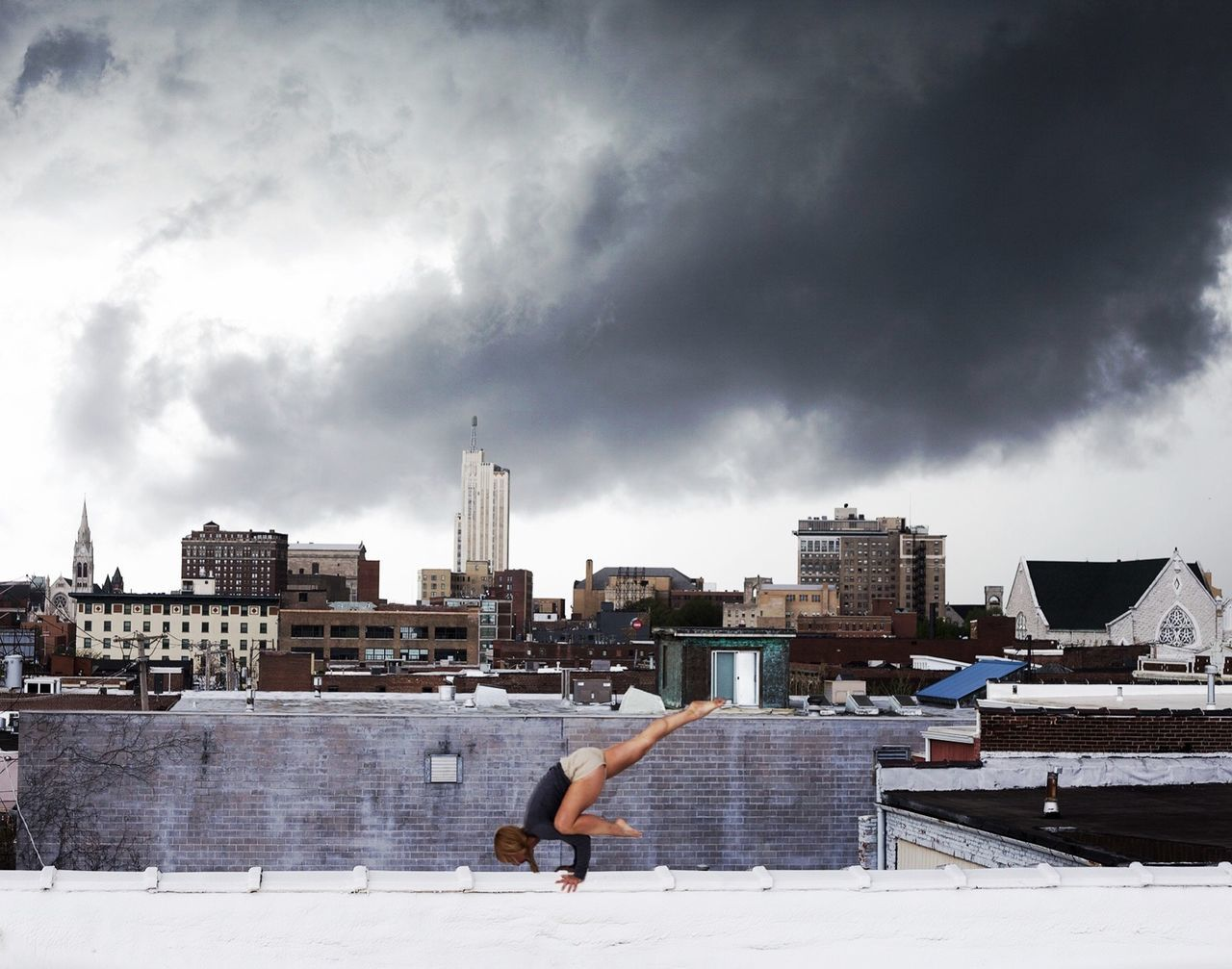 Woman doing yoga on rooftop against cloudy sky