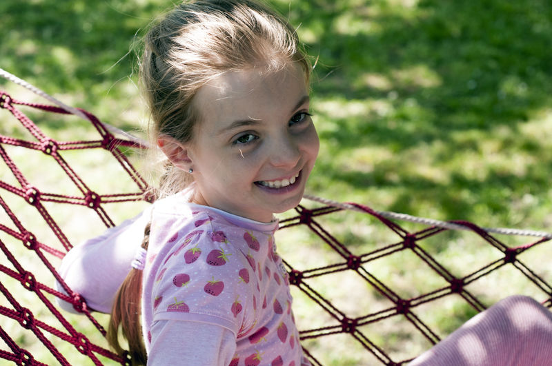 Portrait of smiling girl standing by net