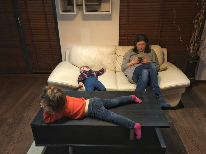 Woman using mobile phone with children on sofa at home