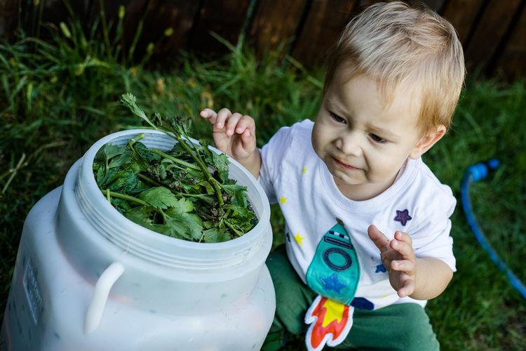 Full length of boy holding plants