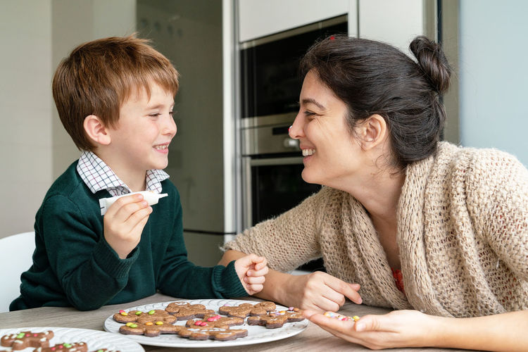 Smiling mother and son making cookies at home