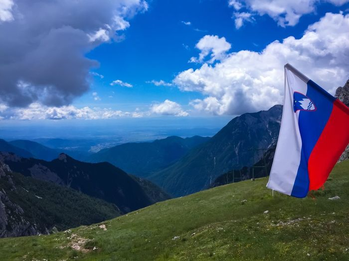A national holiday in the mountains Kamnik-Savinja Alps Valley View Mountain Clouds Hikers Paradise Summer Sky  Mountain Sky Mountain View Hiking Slovenia Slovenian Flag Flag Mountain Cloud - Sky Sky Beauty In Nature Tranquility Scenics - Nature Mountain Range Day No People Blue Patriotism Green Color
