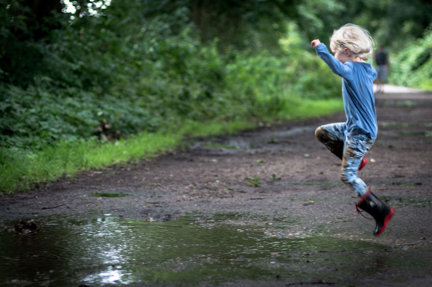 before landing 1 EyeEm Best Shots Fun Jump Kids Kids Being Kids Nature Pure Blond Hair Childhood Children Only Day Dirt Dirty Full Length Girl Jumping Kidsphotography Little Girl Muddy Nature One Person Outdoors Puddle Rubber Boots EyeEm Ready