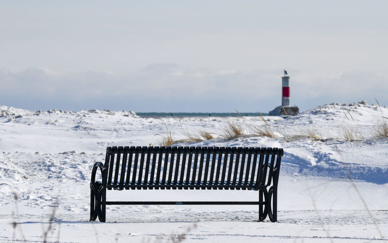 Lighthouse by sea against sky during winter