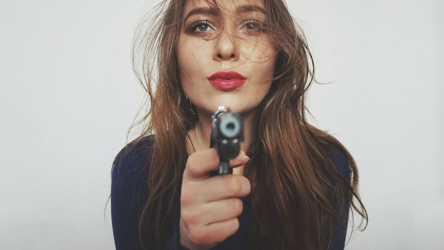 Portrait of woman pointing gun against white background