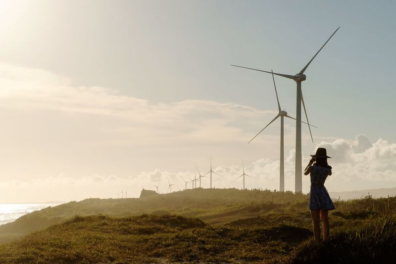 Woman standing on field with wind turbines against sky