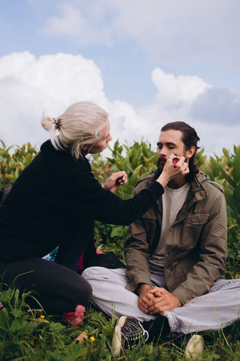 Woman doing make-up on male friend sitting on grass against sky