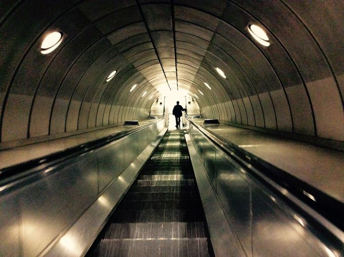 London Underground Arch Architecture Built Structure Ceiling Convenience Diminishing Perspective Direction Illuminated Indoors  Lifestyles Light Lighting Equipment Modern Moving Walkway  One Person Real People Rear View Subway The Way Forward Transportation Tunnel Underpass Walking