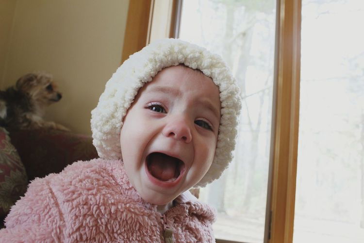 Portrait of cute baby girl shouting at home